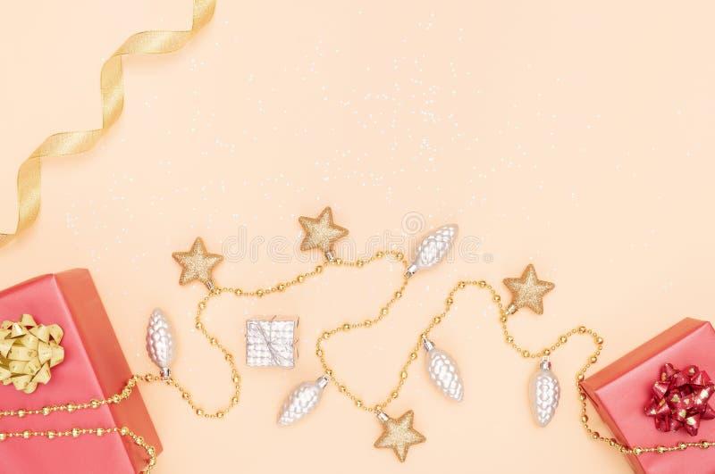礼物盒或提出有红色弓、星和球的箱子在生日、圣诞节或者婚礼的金黄背景 免版税库存图片
