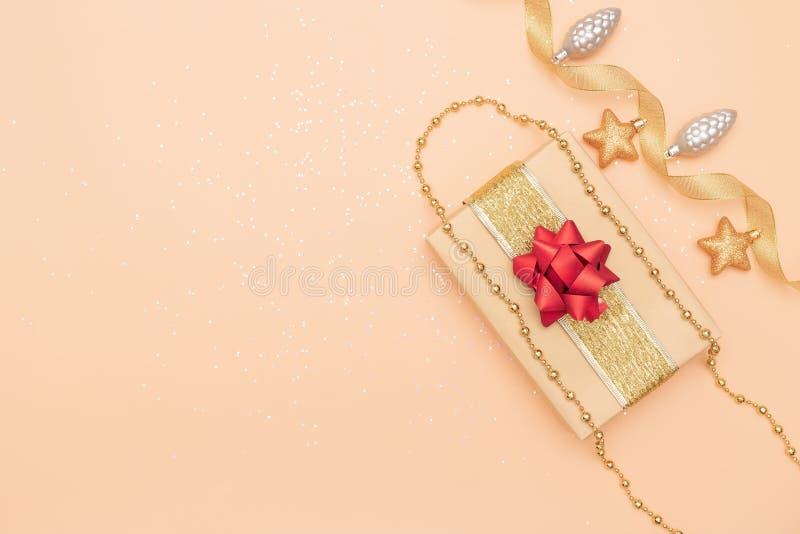 礼物盒或提出有红色弓、星和球的箱子在生日、圣诞节或者婚礼的金黄背景 图库摄影