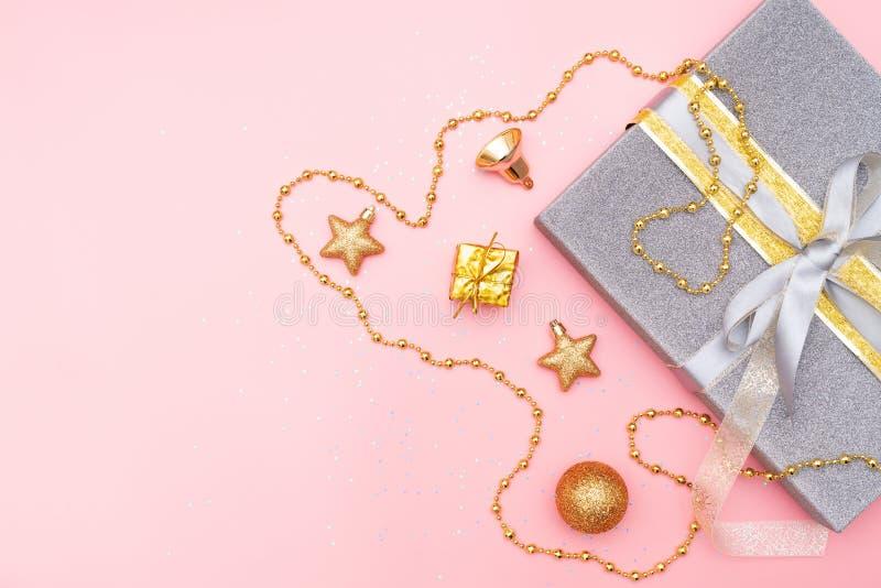 礼物盒或提出有金黄弓、星和球的箱子在生日、圣诞节或者婚礼的桃红色背景 免版税库存照片