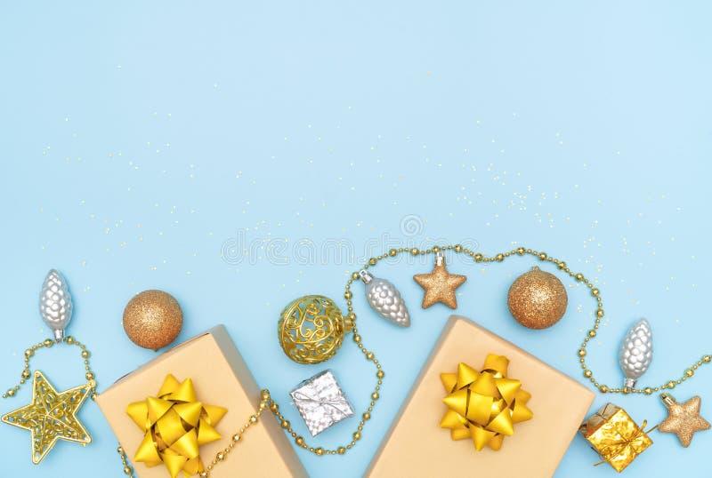 礼物盒或提出有金黄弓、星和球的箱子在生日、圣诞节或者婚礼的蓝色背景 免版税库存照片
