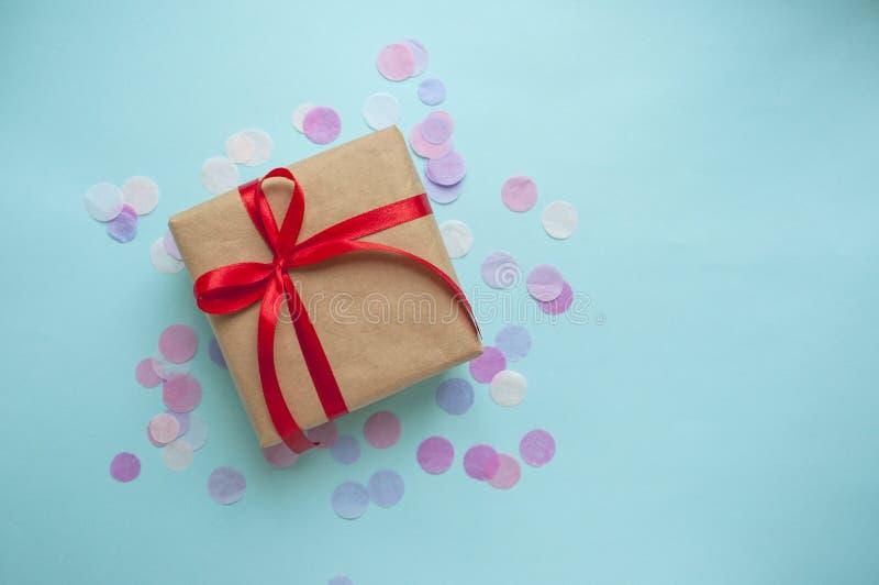 礼物盒栓与在淡色蓝色背景的红色丝带 图库摄影