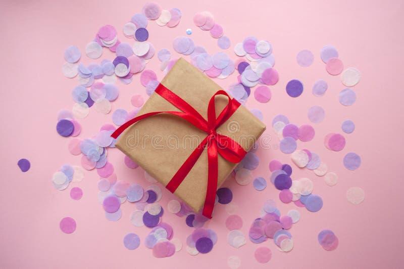 礼物盒栓与在粉红彩笔背景的红色丝带 库存照片