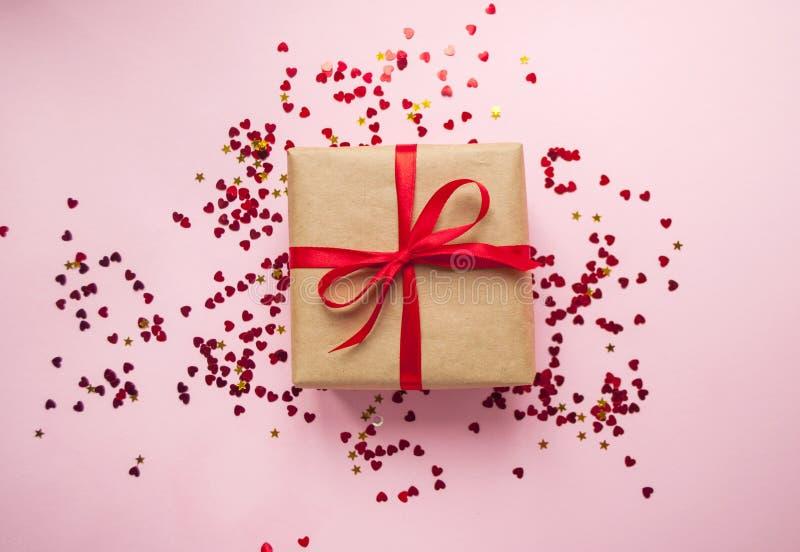 礼物盒栓与在粉红彩笔背景的红色丝带 库存图片