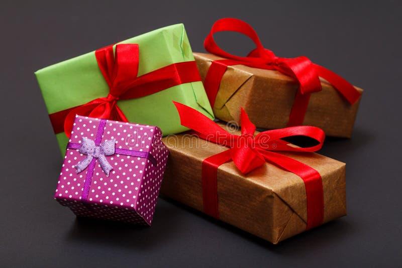 礼物盒栓与在黑背景的红色丝带一 库存照片
