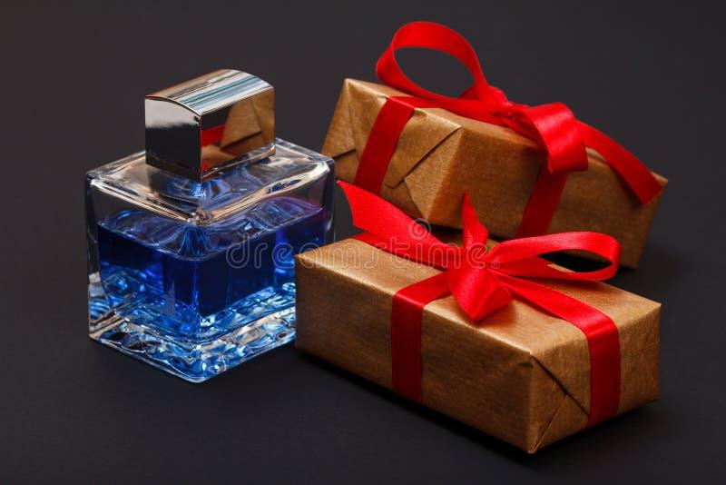 礼物盒栓与红色丝带和瓶在黑背景的香水 库存照片