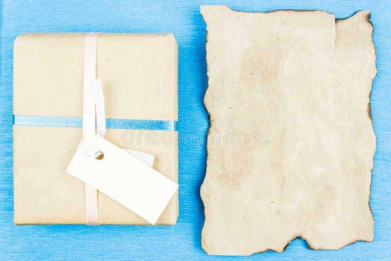 礼物盒由牛皮纸和空白的羊皮纸制成您的文本的在蓝色背景 免版税库存图片