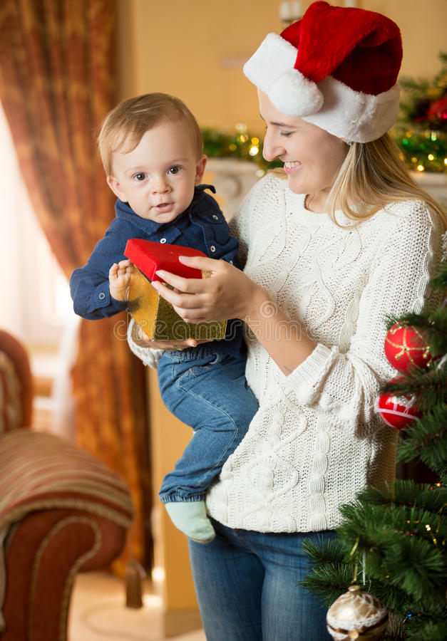 给礼物盒的愉快的年轻母亲她的男婴在圣诞节 免版税库存照片