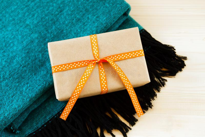 礼物盒被包裹工艺纸和橙色丝带在绿松石和黑羊毛格子花呢披肩在木背景 免版税库存照片