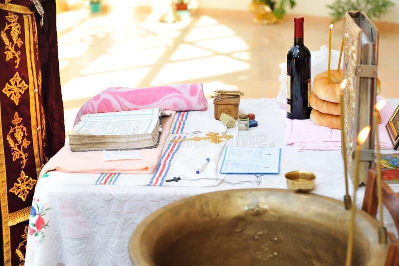洗礼仪式仪式的项目在桌上在教会里。 免版税图库摄影