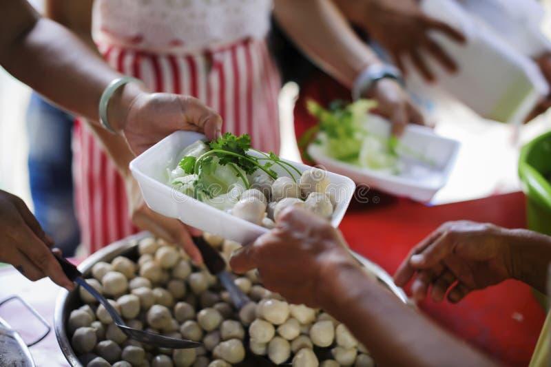 社会分享的概念:接受食物的可怜的人民从捐赠:无家可归的人帮助与救济粮食,饥荒 免版税库存图片