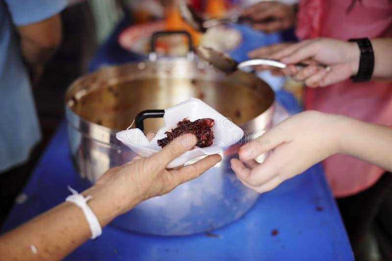 社会分享的概念:接受食物的可怜的人民从捐赠:无家可归的人帮助与救济粮食,饥荒 库存照片