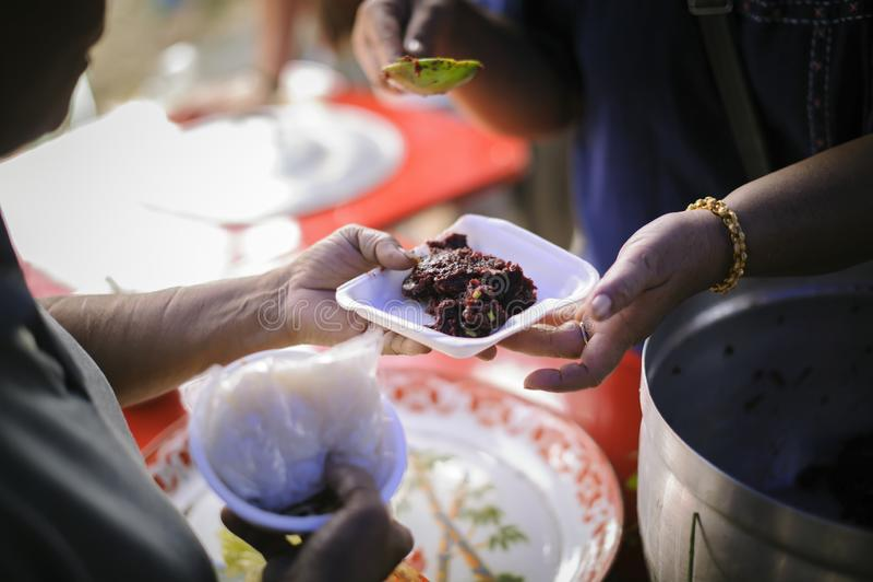 社会分享的概念:接受食物的可怜的人民从捐赠:无家可归的人帮助与救济粮食,饥荒 免版税库存照片