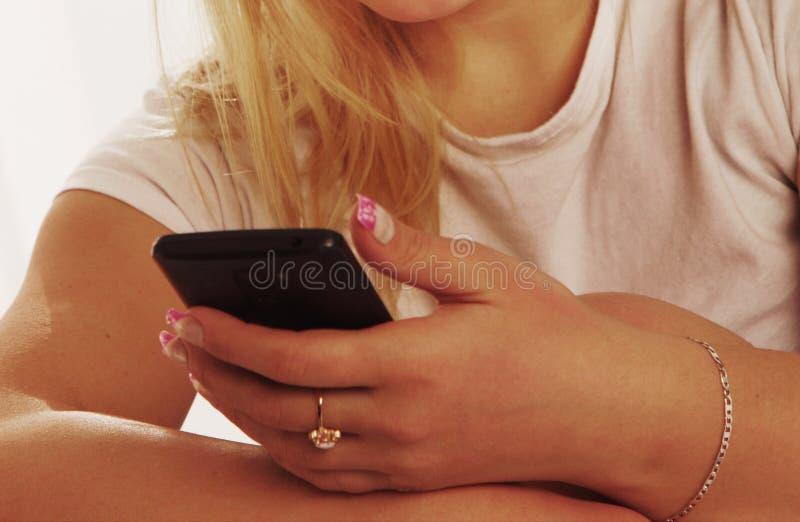 社会媒介瘾 举行smartpho的年轻美丽的妇女 免版税库存图片