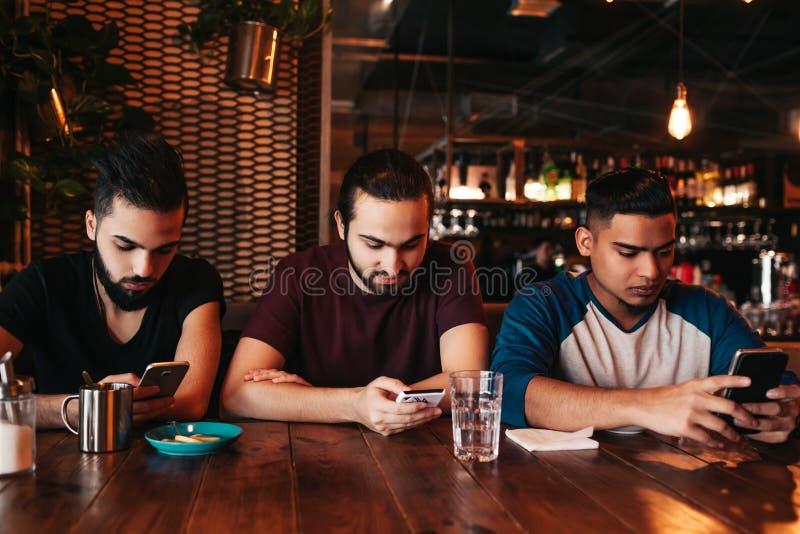 社会网络瘾概念 看他们的在酒吧的混合的族种朋友电话 使用smarphones的阿拉伯人 免版税图库摄影