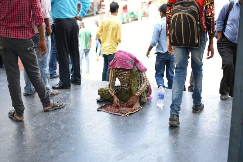 社论:古尔冈,德里,印度:2015年6月07th日:一名未认出的老可怜的妇女乞求从人在古尔冈地铁站乐团 库存照片