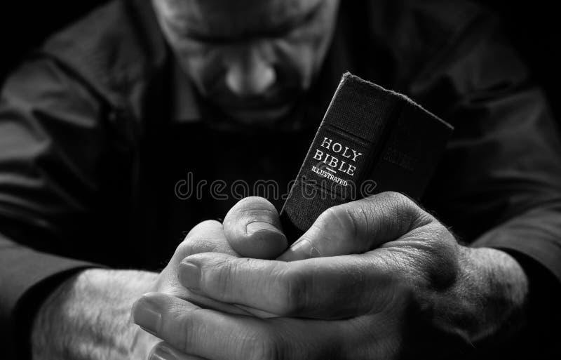 祈祷一个的人拿着圣经。 图库摄影