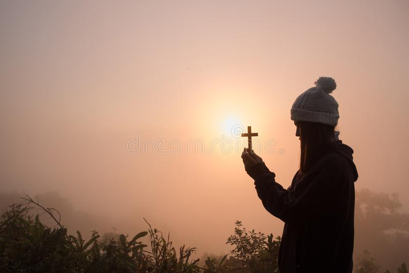 祈祷与十字架的年轻女人剪影在日出,基督徒宗教概念背景 免版税图库摄影