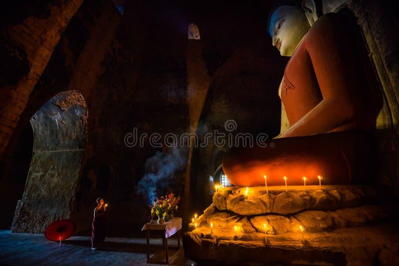 祈祷与在Buddihist寺庙的蜡烛光的东南亚初学者 图库摄影