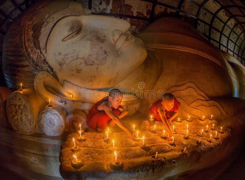 祈祷与蜡烛的未认出的年轻佛教修士点燃 免版税库存照片