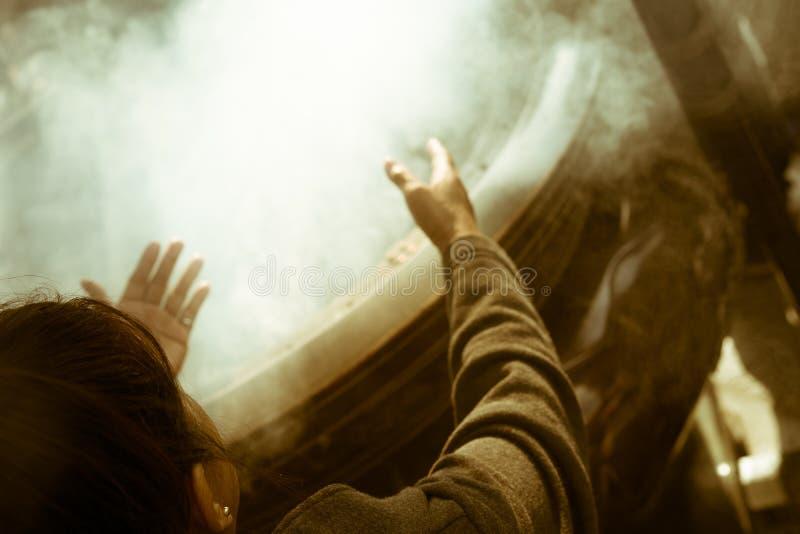 祈祷与香火的妇女烧在著名佛教寺庙Senso籍在浅草,东京,日本 免版税库存照片