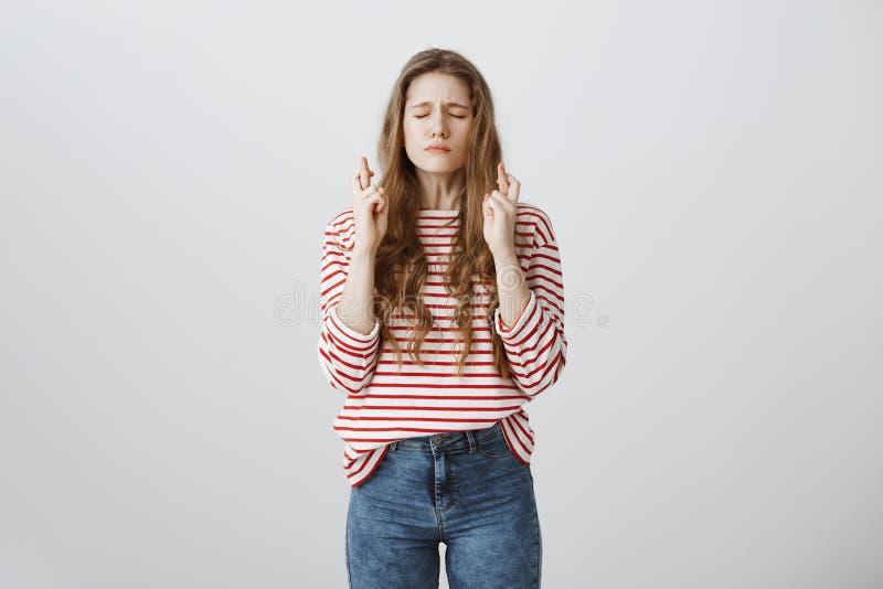 祈祷为通过的怯懦和担心的学生检查 悦目年轻欧洲女孩画象有纹身花刺结束的 库存照片