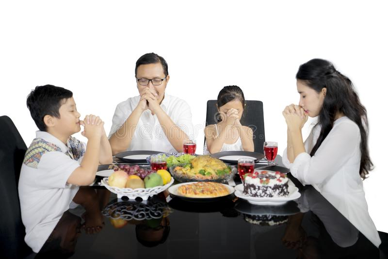 祈祷以前吃的基督徒家庭在演播室的晚餐 免版税库存照片