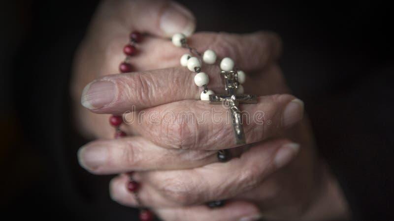 祈祷和拿着念珠的老手 库存图片