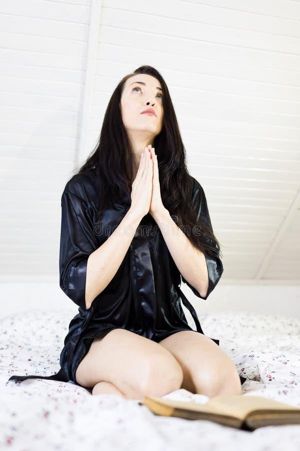 祈祷在与圣经的床上的可爱的妇女 免版税图库摄影