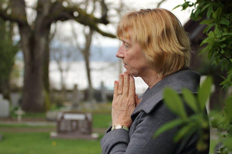 祈祷在亲人的公墓 库存图片