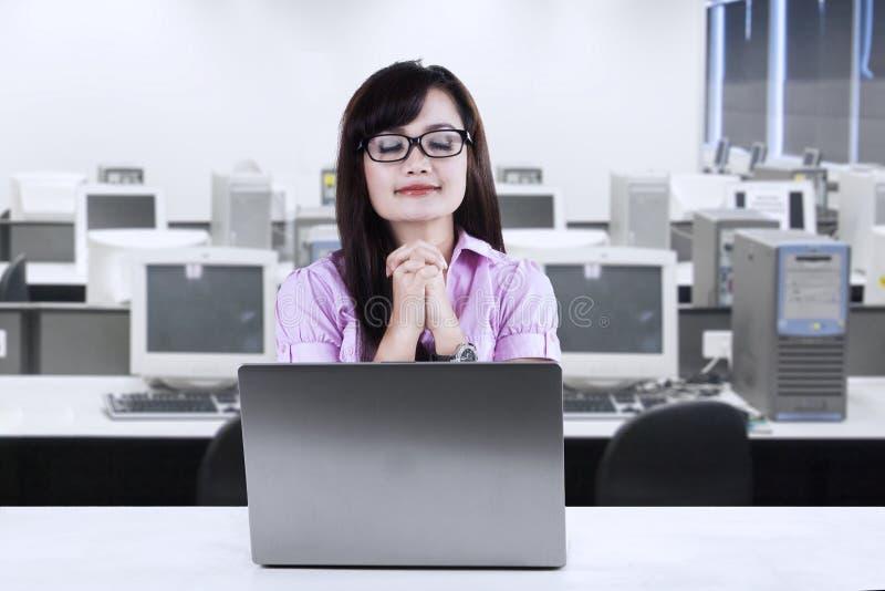 祈祷在办公室的年轻女实业家 免版税库存图片