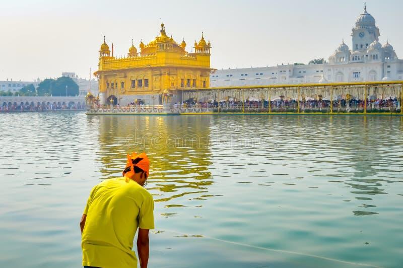 祈祷在圣洁坦克的锡克教徒的香客在金黄寺庙Sri Harmandir Sahib,阿姆利则,印度附近 库存照片