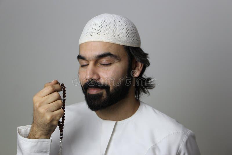 祈祷在圣洁月的一个回教阿拉伯男性模型斋月穆斯林祈祷斋月阿拉伯人 免版税库存照片