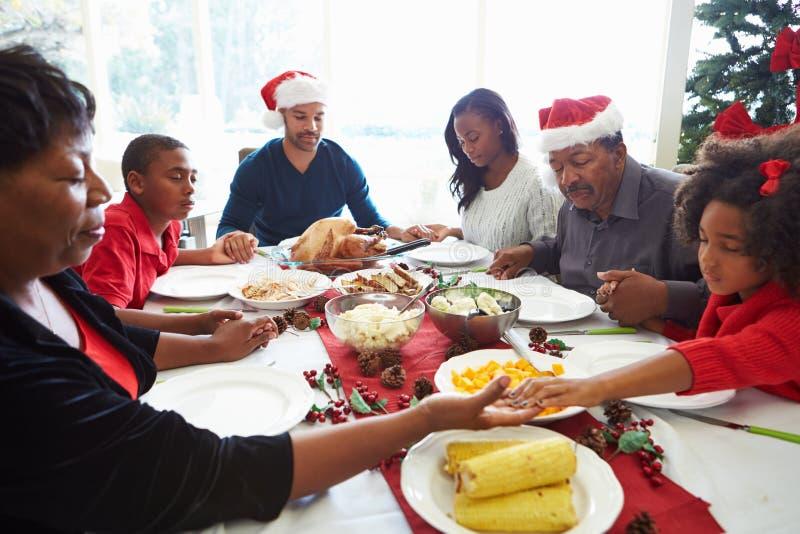 祈祷在圣诞节膳食前的多一代家庭 免版税库存图片