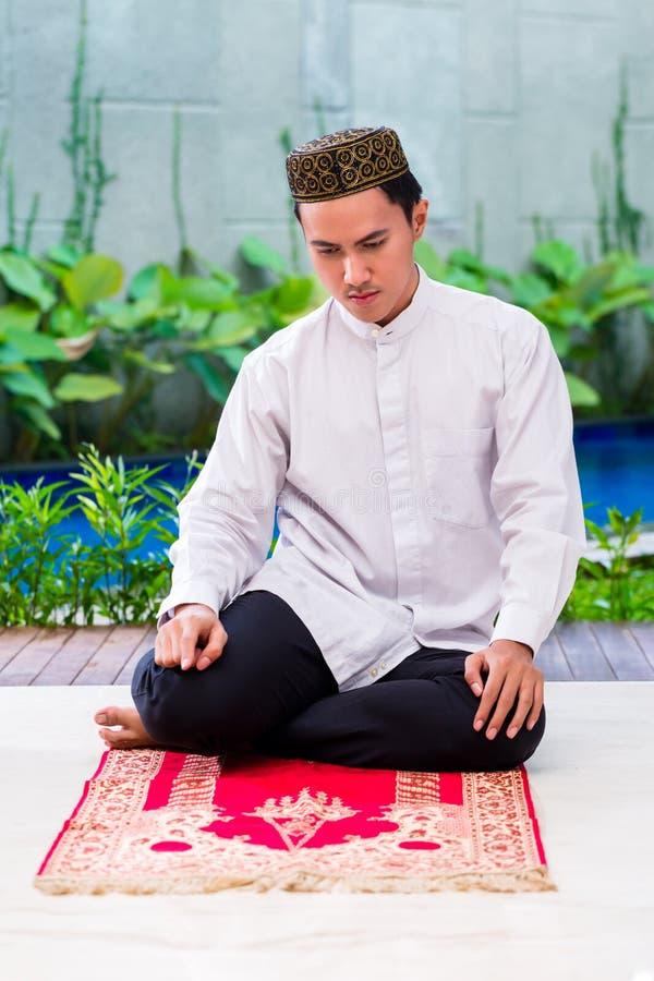 祈祷在地毯的亚裔回教人 免版税库存图片
