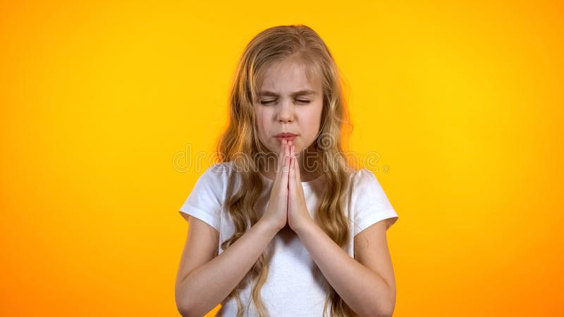 祈祷在学校检查前的滑稽的白肤金发的女小学生,要求慈悲,幼稚信仰 图库摄影