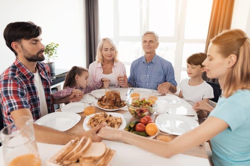 祈祷在感恩的晚餐前的家庭 免版税库存照片