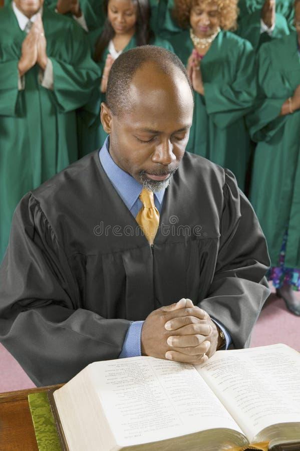 祈祷在教会里的传教者和唱诗班 免版税库存图片