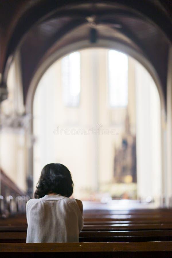 祈祷在教会里的少妇背面图 免版税库存图片