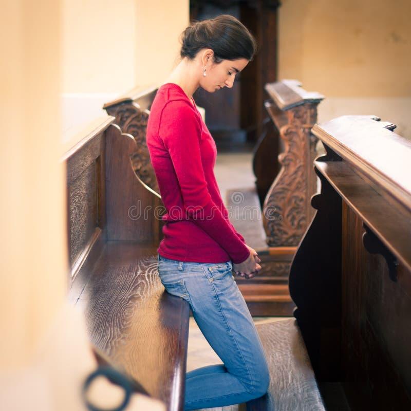 祈祷在教会里的少妇 免版税库存图片