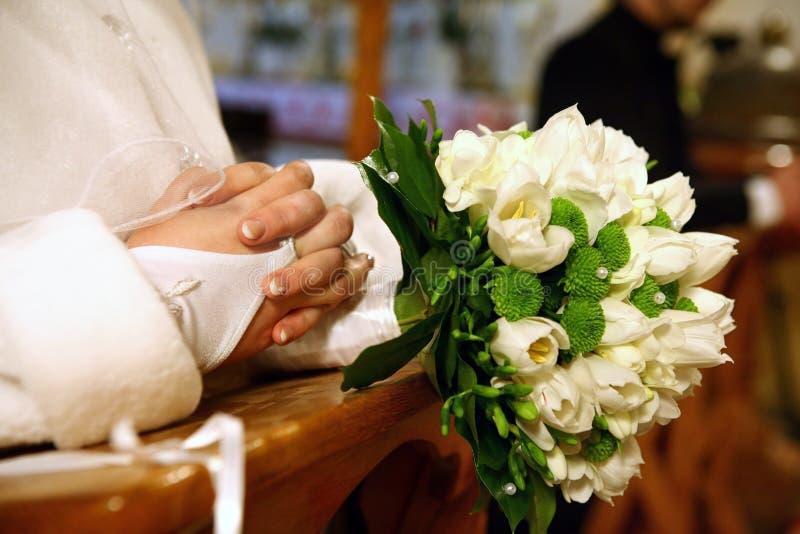 祈祷在教会里的新娘和新郎在婚礼 免版税库存图片