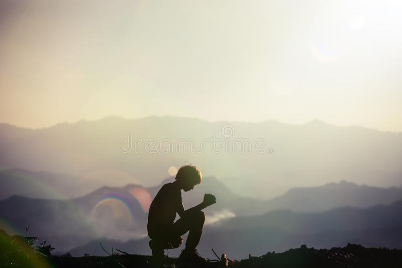 祈祷在日落的剪影年轻亚裔基督徒人 免版税库存照片