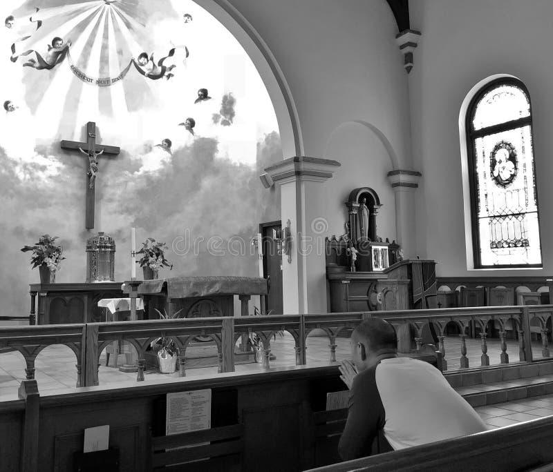 祈祷在有美好的彩色玻璃和十字架的一个宗教教会里面的人 图库摄影