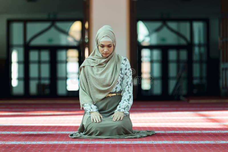 祈祷在清真寺的年轻美丽的回教妇女 库存图片