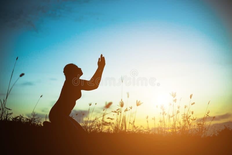 祈祷在美好的天空背景的妇女剪影 库存照片