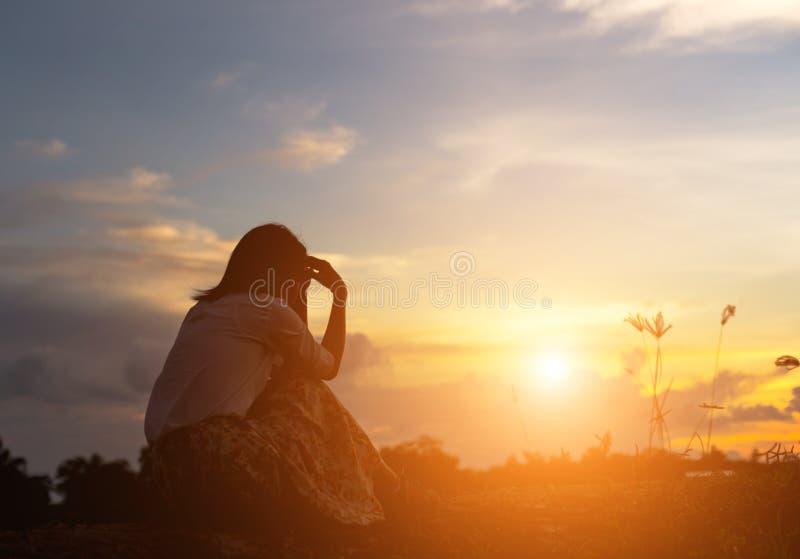 祈祷在美好的天空背景的妇女剪影 免版税库存照片