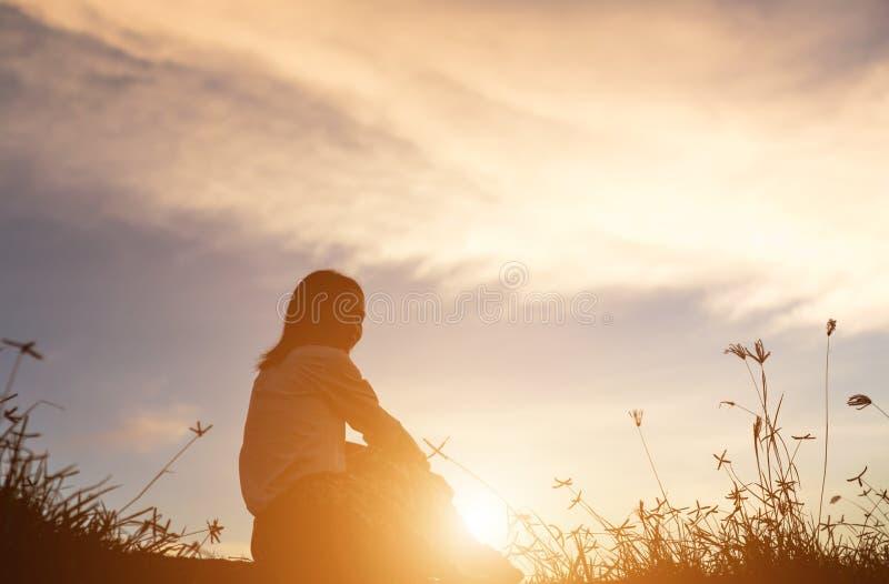 祈祷在美好的天空背景的妇女剪影 库存图片