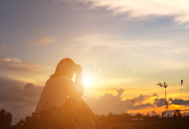 祈祷在美好的天空背景的妇女剪影 图库摄影