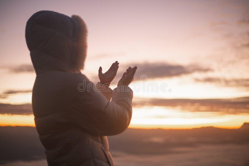祈祷在美好的日出背景影像的妇女剪影 免版税库存图片