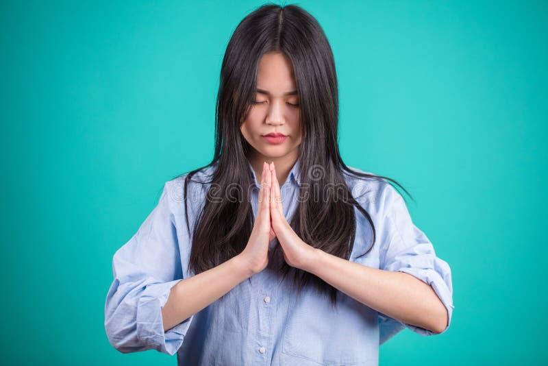 祈祷在蓝色演播室背景的亚裔少妇 免版税库存照片