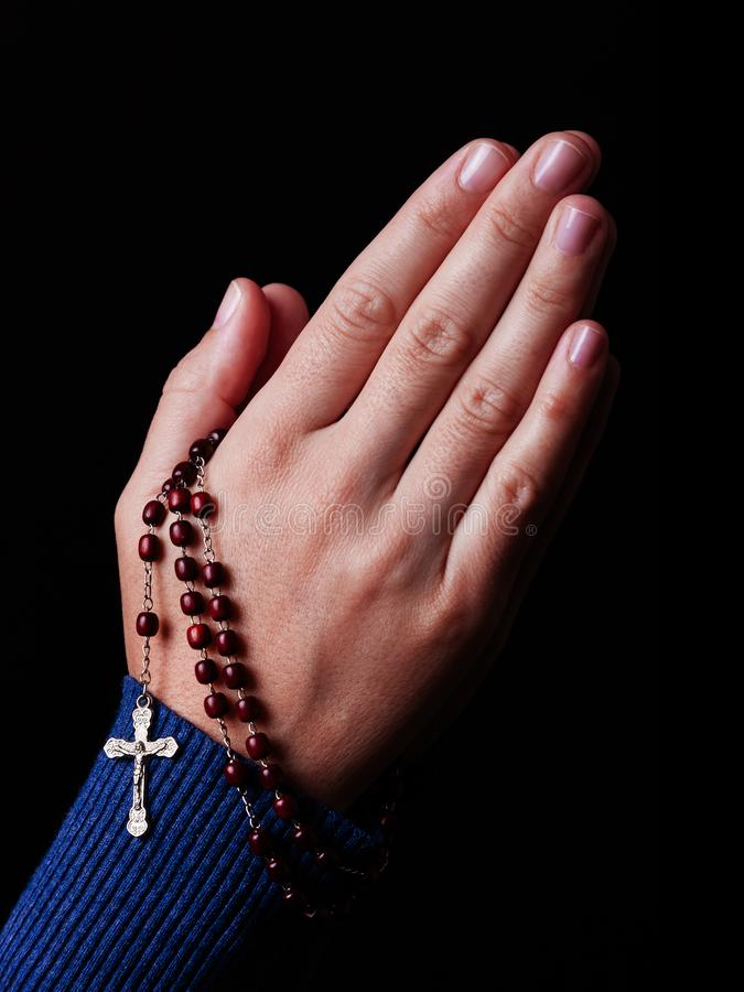 祈祷女性的手拿着有耶稣基督的一个小珠念珠十字架或耶稣受难象的 免版税库存照片